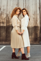 beautiful female models in turtle necks and skirts holding hands at urban street
