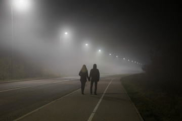 Young couple holding each other hands. Slowly walking under white street lights in night. Dark time. Peaceful atmosphere in mist. Foggy air.