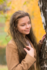 Girl-teenager in a coat stands in the autumn park at a yellow foliage background.