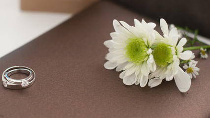 Colorful pictures with wedding rings on the back of the flower bouquet.