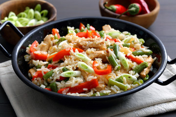 riso con verdure e carne arrosto in tagame di metallo su sfondo grigio