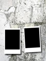 Two blank rectangular instant photo frames on white marble stone wall background