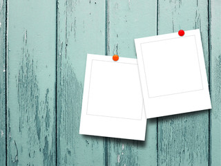 Two blank square instant photo frames on turquoise wooden boards background