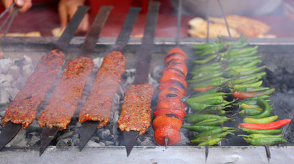 Adana Kebabs cooking with Tomatoes and Green Peppers on charcoal grill