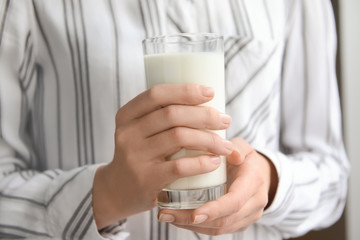 Woman holding glass of tasty milk, closeup