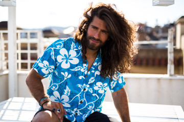 young man with long hair wearing a shirt posing