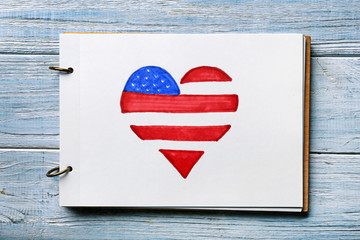 Sheet of paper with heart shaped drawing of American national flag on wooden table