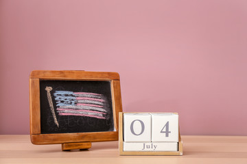 Chalkboard with drawing of American national flag and calendar on wooden table. 4th July celebration