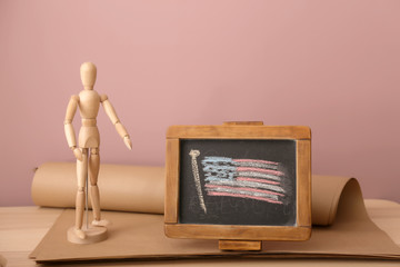Chalkboard with drawing of American national flag and small mannequin on wooden table