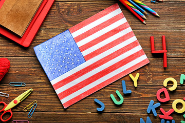 Drawing of American national flag with color letters and stationery on wooden table. 4th July celebration