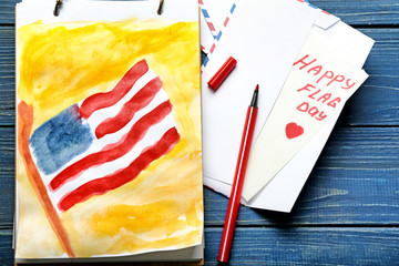 Sheet with painting of American national flag and envelops on color wooden table