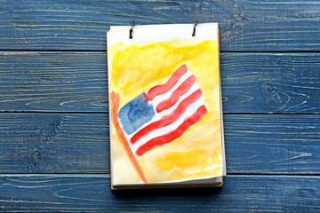 Sheet with watercolor painting of American national flag on color wooden table