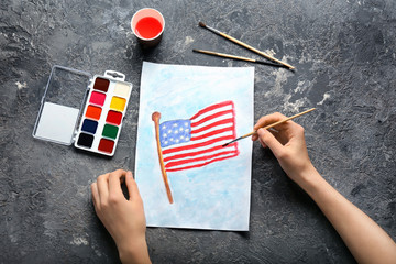 Woman painting American national flag on sheet of paper