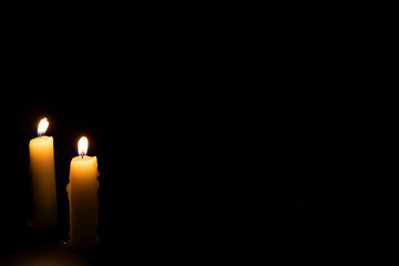 Two candles on dark background. Lighting candles on black. Yellow wax candle with warm flame.