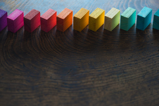 Colored wooden blocks diagonally aligned on old vintage wooden table. For something with concept of variations or diversity. Plenty of copyspace for cover / header image usage. Shallow depth of field.
