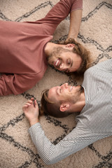 Young LGBT couple lying on floor