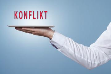 Tablet mit dem Wort Konflikt