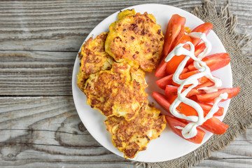 Chicken breasts coated with cheese, tomatoes on white plate, on old wooden table