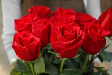 Saleswoman holding bouquet of beautiful roses, closeup
