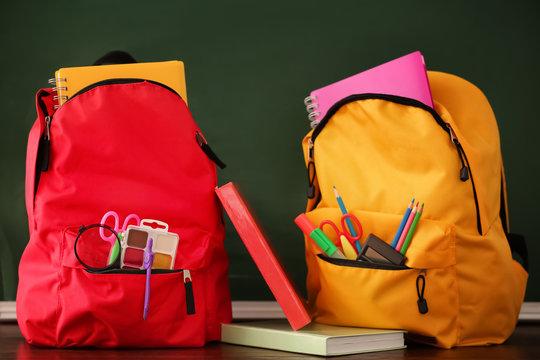 Backpacks with school supplies near chalkboard