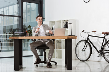 handsome happy businessman with cup of coffee sitting at workplace in modern office