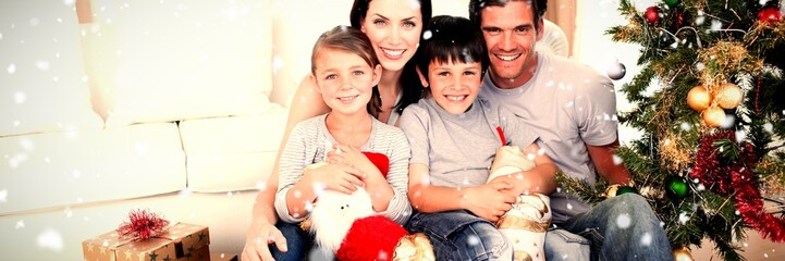 Composite image of happy family at christmas time holding lots