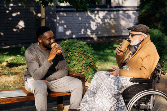 senior disabled man in wheelchair and african american man drinking coffee from paper cups together on street