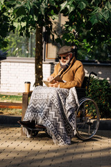 senior disabled man in wheelchair with paper cup of coffee reading book on street