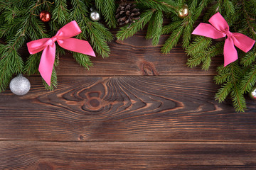 Christmas background with fir branches and pink ribbon bow and christmas balls.