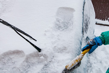 Cleaning snow from car with brush