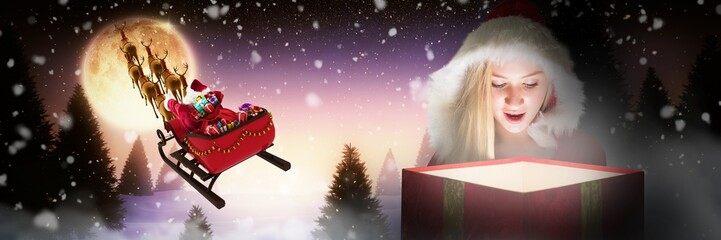 Composite image of festive blonde looking into glowing gift