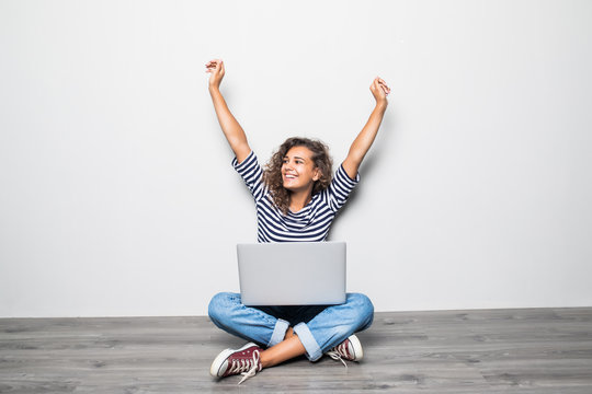 Portrait of happy young mixed races curly woman sitting on floor with laptop and celebrate win