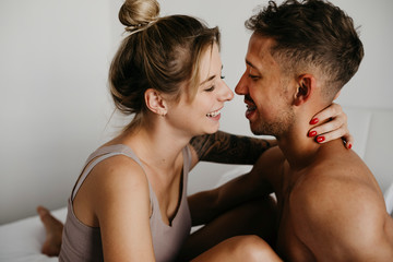 Happy young couple in bed smiling at each other