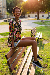 Portrait of smiling young woman sitting on bench in a park