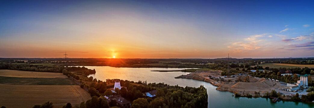 Luftbild eines Baggersees im Sonnenuntergang