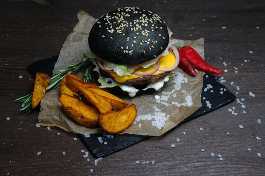 black burger on plate on woon table