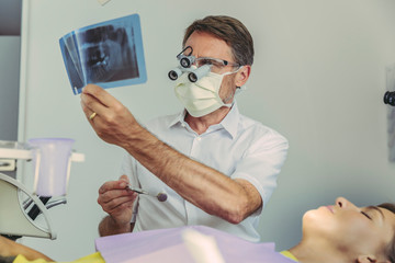 Dentist looking at x-ray image before treatment