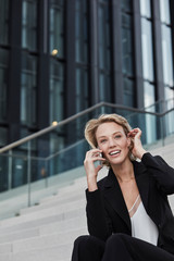 Portrait of smiling young businesswoman on the phone sitting on stairs outdoors