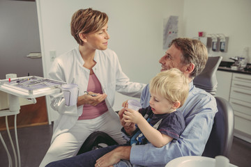 Female dentist talking to patient with son sitting on his lap