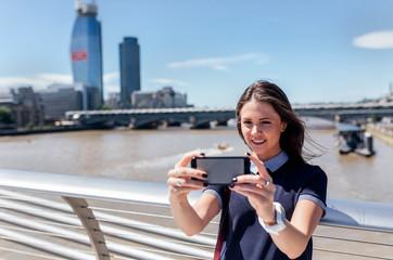 UK, London, woman taking a selfie on the Millennium Bridge