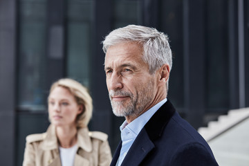 Portrait of mature businessman with grey hair and beard outdoors