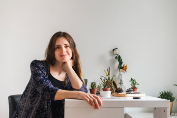Portrait of smiling young woman at home surrounded by plants