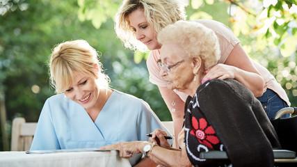 Seniorin beim Kreuzworträtzeln mit Tochter und Pflegerin