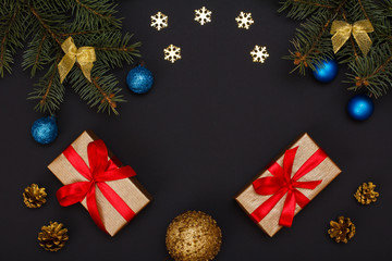 Gift boxes, fir tree branches with cones on black background