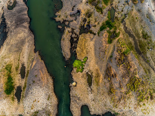 Top view aerial photo of green river pattern with sediment bar