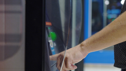 ATM Banking Hand Enter Pin Code In Cash Machine. Male hand typing personal pin code in a ATM cash machine. close up shot
