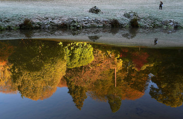 A visitor and autumn foliage are reflected in the lake at Stourhead gardens in Wiltshire