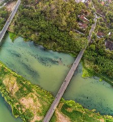 Long bridge aerial top view with wide river, green trees, and small village
