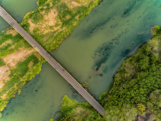 Long bridge aerial top view with wide river and green trees