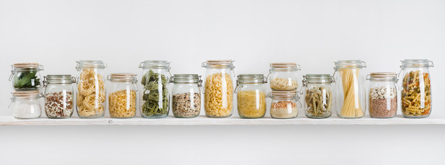 Assortment of uncooked groceries in glass jars arranged on shelf